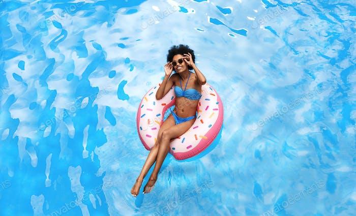 Sommerzeit. Schöne schwarze Frau im Bikini schwimmen auf aufblasbaren Ring am Pool während tropischen