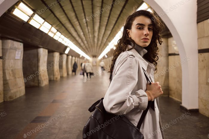 Beautiful girl in trench coat with backpack confidently looking in camera at subway station