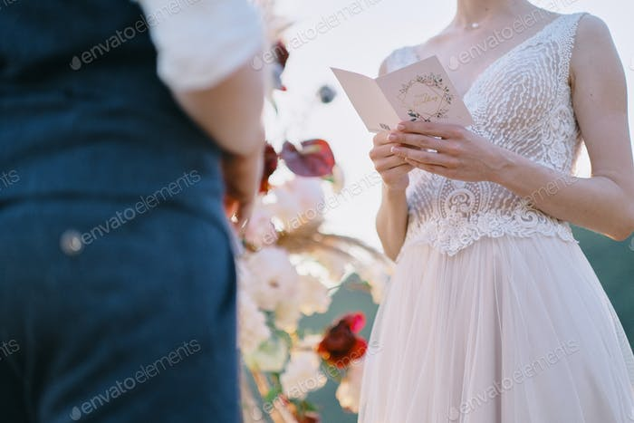 The bride reads a wedding speech to groom. Beautiful moment from a wedding ceremony in nature.