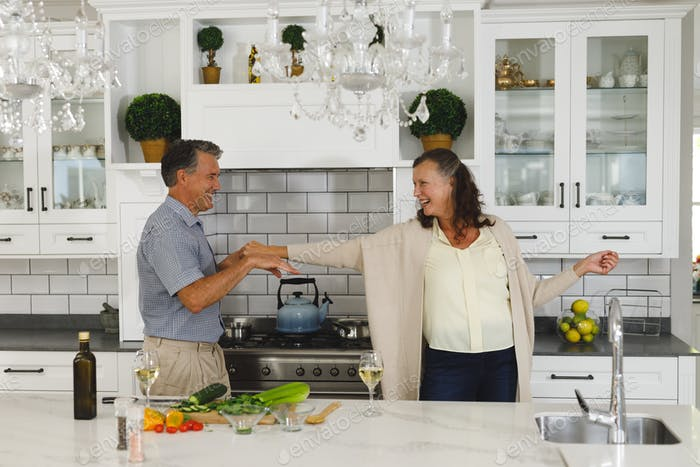 Happy senior caucasian couple in modern kitchen, dancing together and smiling