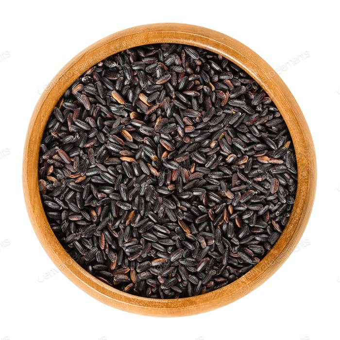 Organic black rice in wooden bowl over white