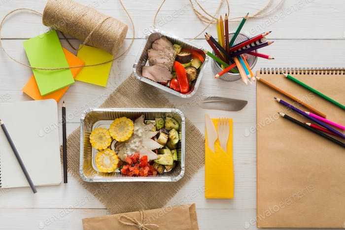 Healthy food in foil box on working table, diet concept.