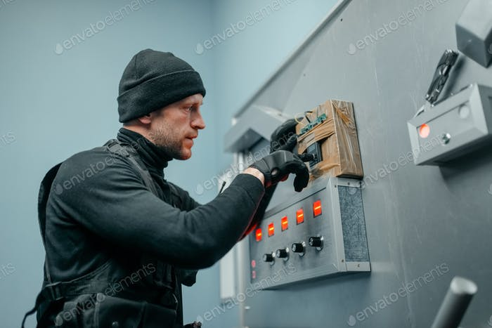 Robber in uniform trying to mines the vault door