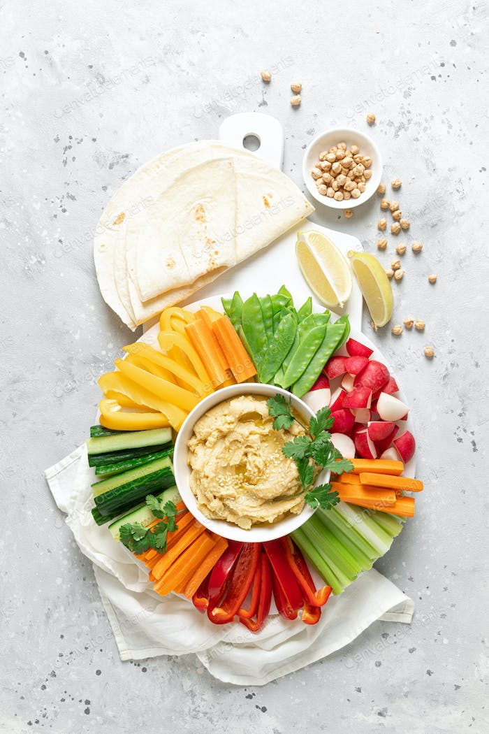 Hummus with fresh vegetables, healthy vegetarian food concept, top view