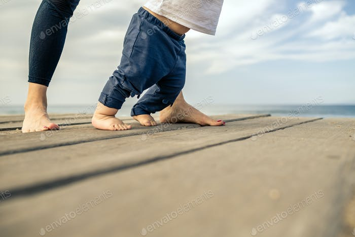 Baby boy walking on the beach in beautiful summer day
