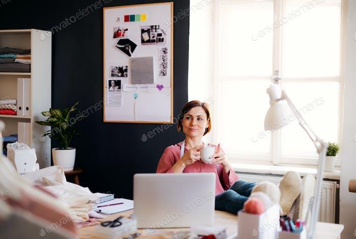 Junge kreative Frau in einem Atelier, ruht. Ein Start-up des Schneidergeschäfts.