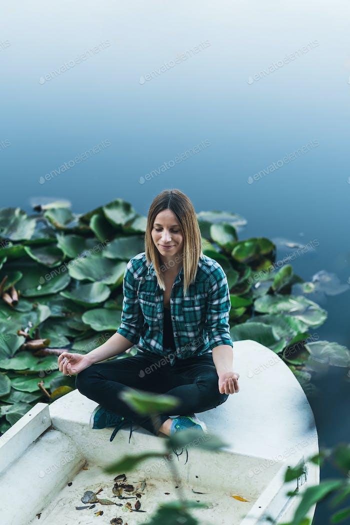 Peaceful young woman meditating in lotus pose