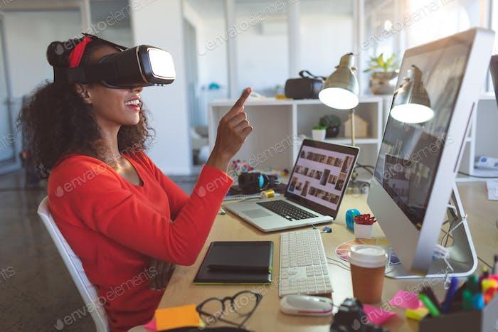 Weibliche Grafikdesignerin mit Virtual Reality Headset am Schreibtisch in einem modernen Büro