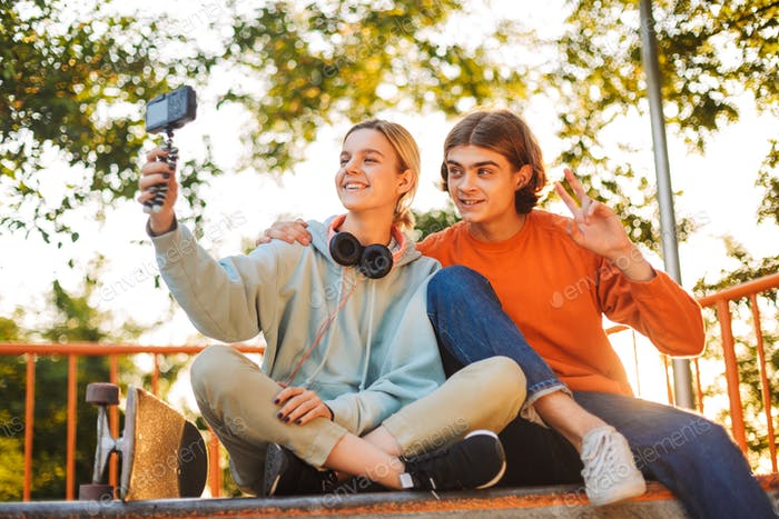 Young smiling skater boy and girl with headphones happily record