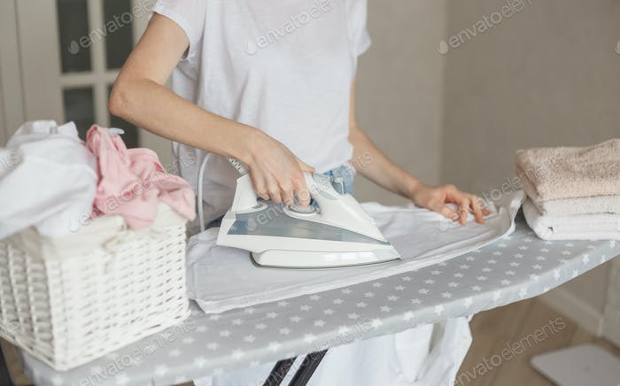 Woman ironing white clead washed shirt at home