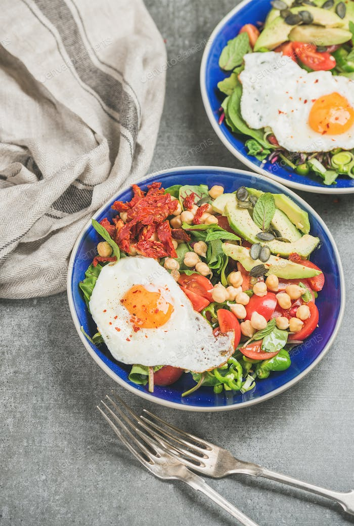 Healthy breakfast with fried egg, chickpea, vegetables, seeds and greens