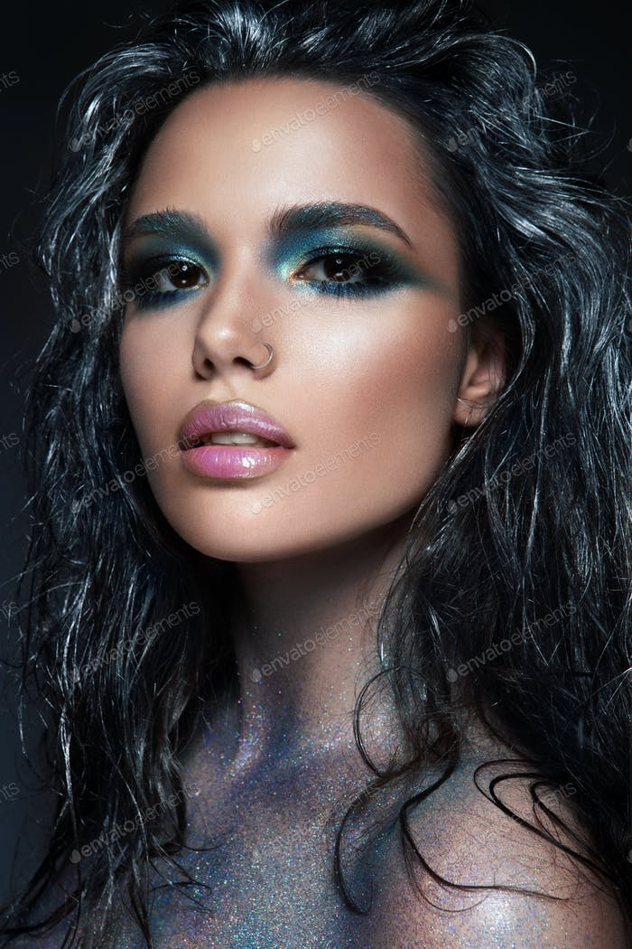 Beautyful girl with blue glitter on her face