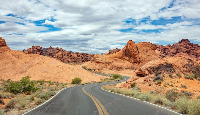 Long winding highway with ups and downs, cloudy blue sky. Valley of Fire Nevada, USA