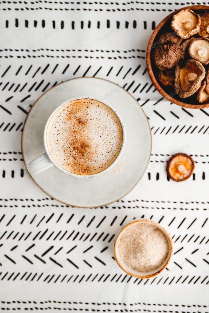 Draufsicht auf Cappuccino Kaffee mit Shiitake-Pilzpulver. Immun- und Gesundheitsgetränk.