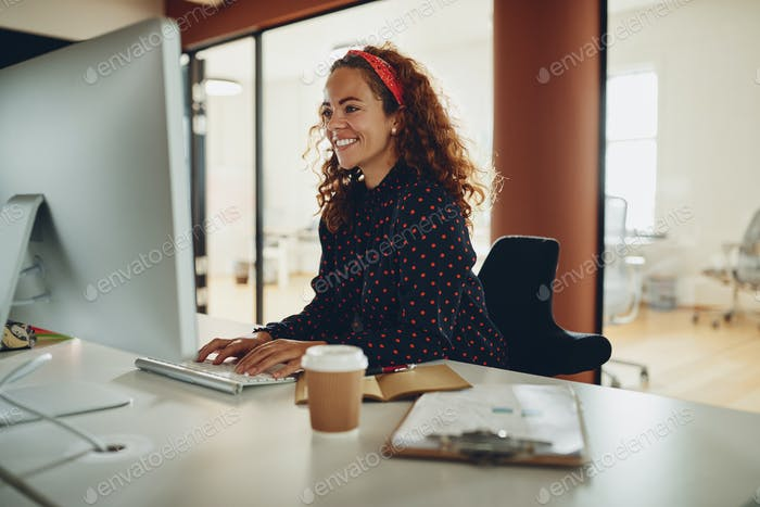 Smiling young businesswoman working late in her office