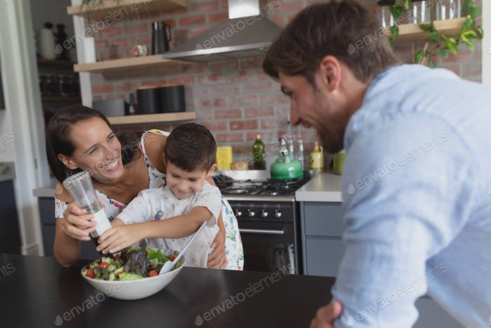 Side view of happy Caucasian family preparing vegetable salad in kitchen at home
