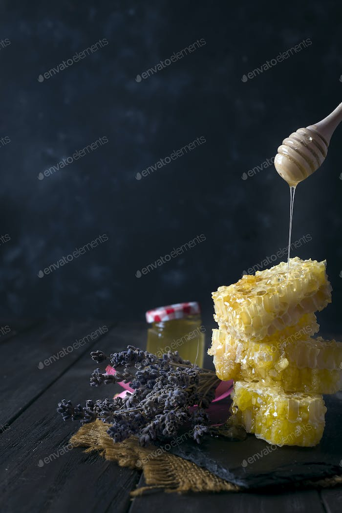 pouring honey into honey comb with lavender flowers on stone dark background