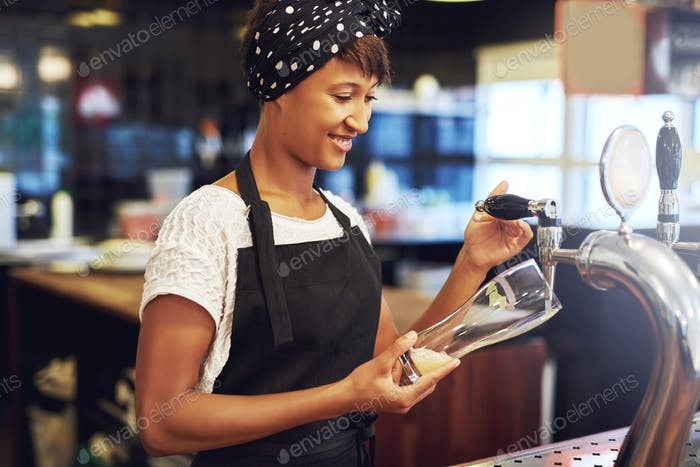 African American bartender pouring a glass of beer