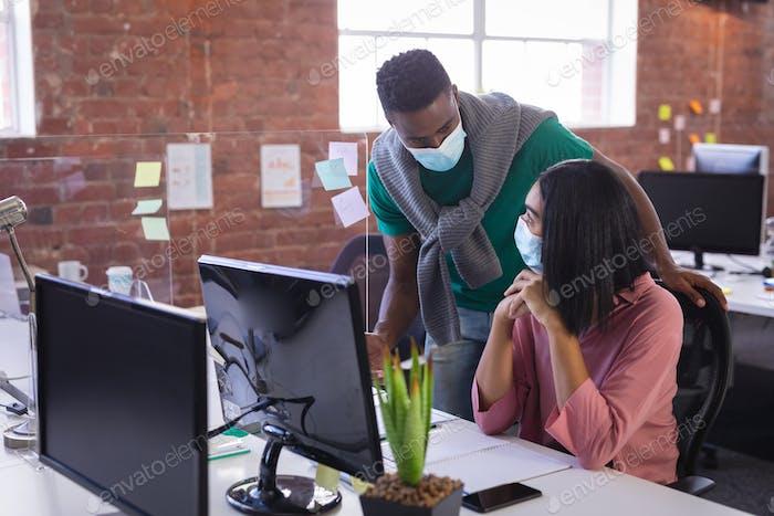 Diverse Geschäftskollegen mit Gesichtsmasken vor dem Computer