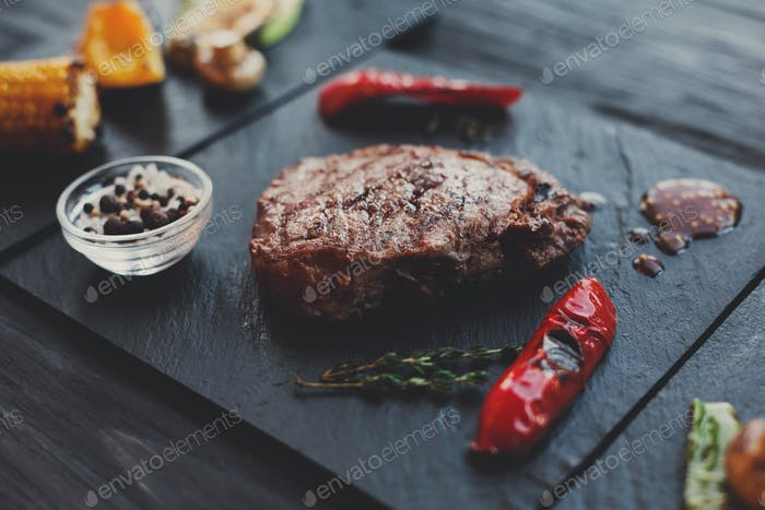 Grilled beef steak closeup on dark wooden table background