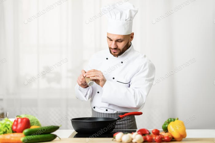 Chef Adding Pepper In A Pan Seasoning Food In Kitchen