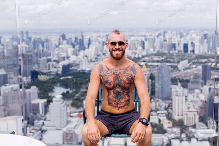 tattooed strong man topless, with watch, sits on chair on high floor