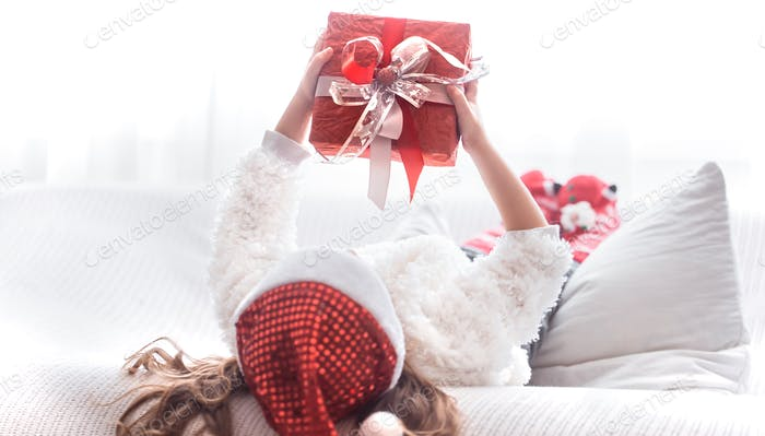 Little girl with Christmas gift in Santa costume