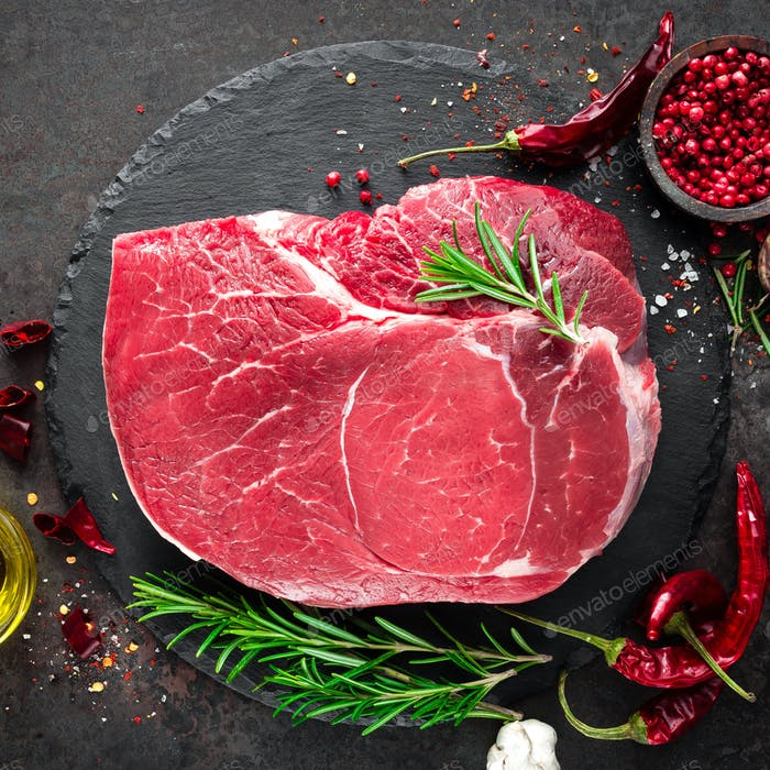 Raw beef steak on black background with cooking ingredients. Fresh beef meat. Top view