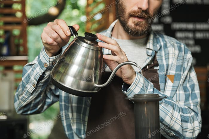 Portrait of professional barista man making coffee while working