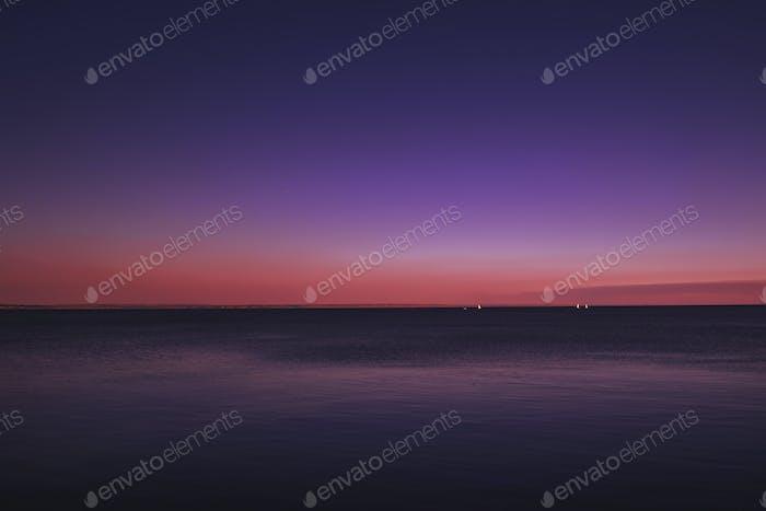 Blaues Meer, rosa orange Himmel bei Sonnenuntergang. Sommer Meer malerische Landschaft am sonnigen Abend