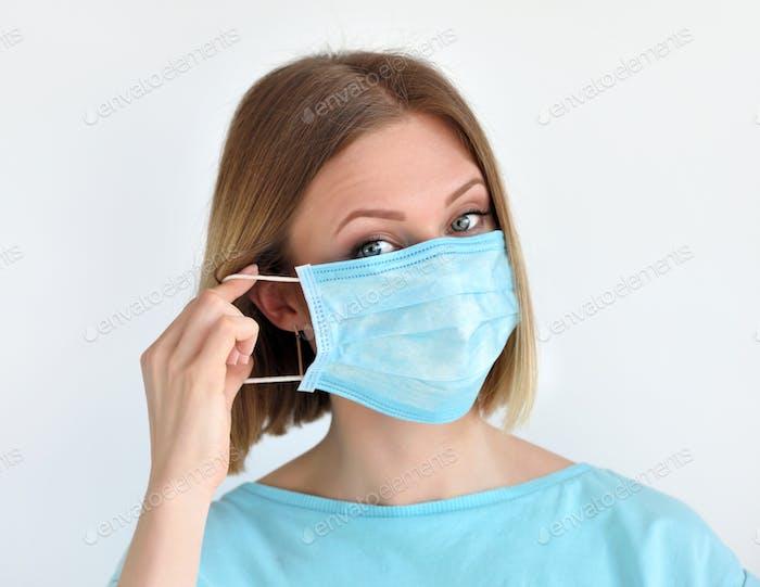 Chica pone una máscara facial médica para la protección contra la infección. Concepto médico y sanitario.