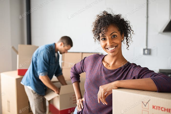 Woman leaning on cardboard box while moving house