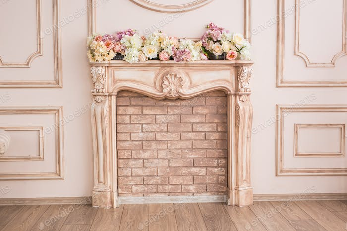 Beautiful beige fireplace with decorative flowers close-up