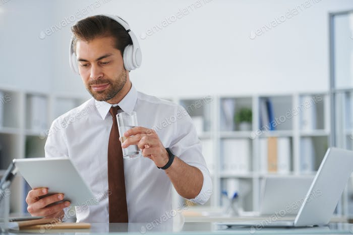 Young serious businessman in headphones looking at tablet screen