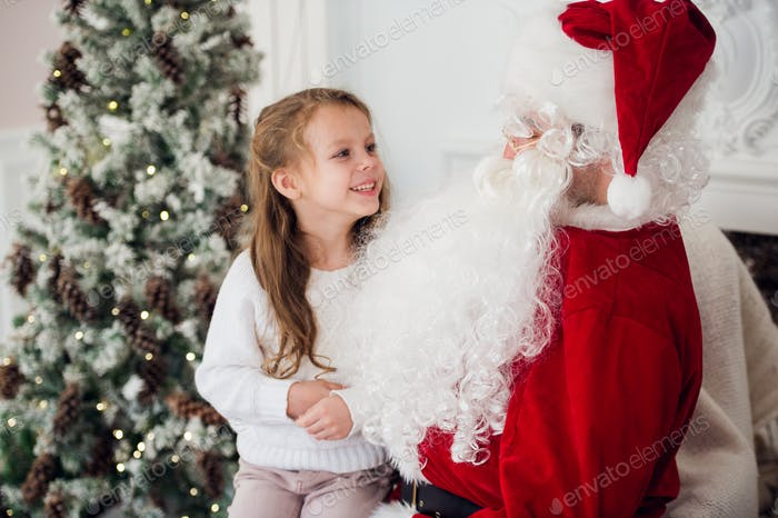 dream is real in christmastime. happy little cute girl sitting on the lap of aged Santa Claus and
