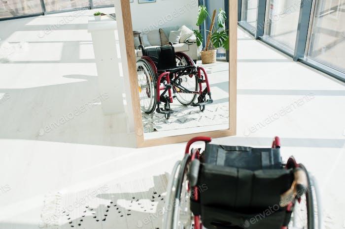 Empty wheelchair at home. Wheel chair indoor in mirror.