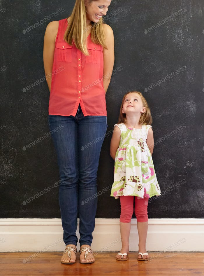 Little girl standing with her mother at home
