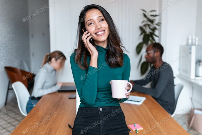 Young indian business woman entrepreneur talking on mobile phone in the office.