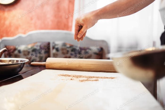 Male chef hand over dough, apple strudel cooking