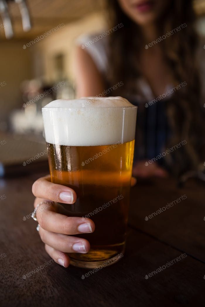 Close-up of barmaid holding beer glass