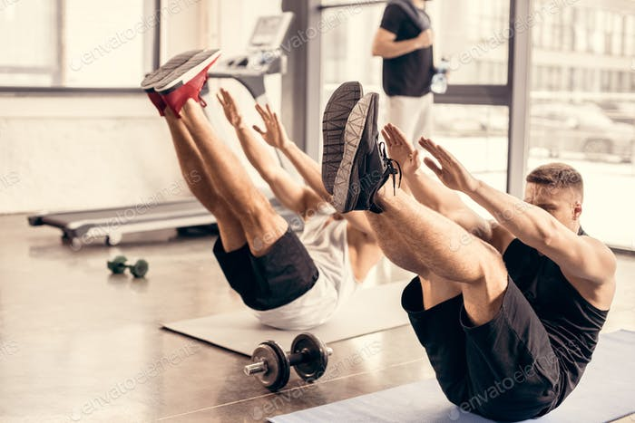 sportsmen simultaneously exercising on yoga mats in gym