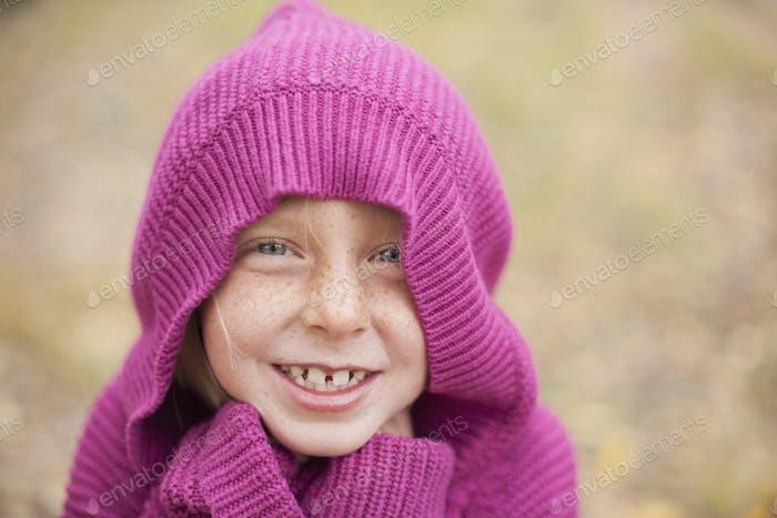 Ein Mädchen in einem magentafarbenen Kapuzenpullover, warm zu halten.