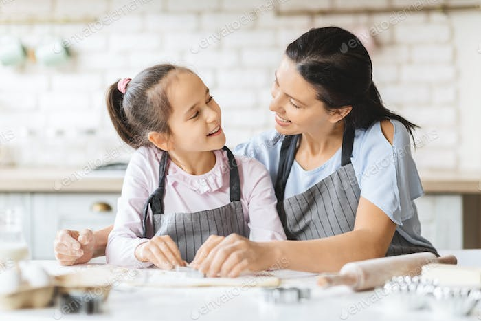 Portrait of happy mother and daughter cooking together in kitchen