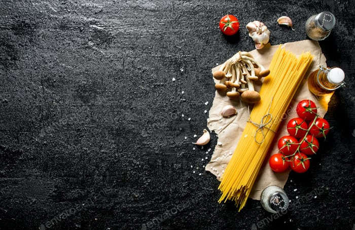 Raw spaghetti on paper with mushrooms, spices and tomatoes on a branch.