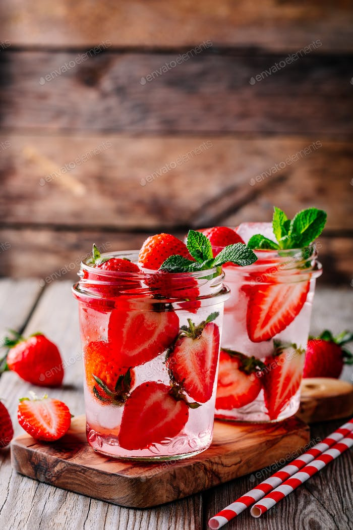 Detox water with strawberry and mint. Ice cold summer cocktail or lemonade in glass mason jar