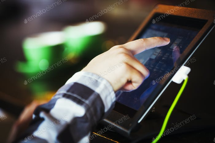Specialist coffee shop. A person using a touch screen at a till.