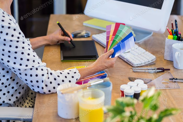Casual businesswoman looking at colour swatch and drawing with digitizer in the office