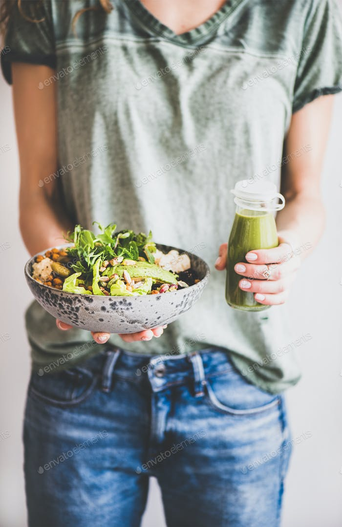 Woman in jeans holding healthy superbowl and smoothie in hands