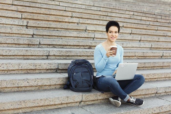 Улыбающаяся женщина сидит на лестнице с помощью ноутбука