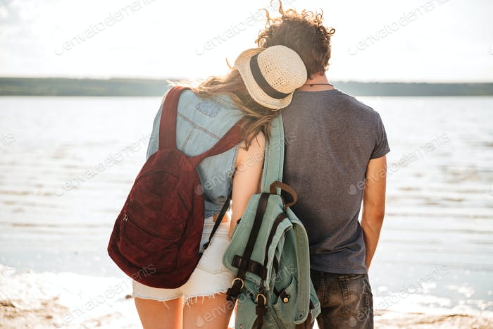 Young couple standing backwards hugging and looking at the seaside